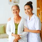 caregiver hugging senior woman indoor